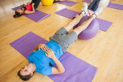 Class exercising with fitness balls at a bright gym - stock photo