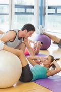 Stock Photo of Trainer helping woman at fitness studio