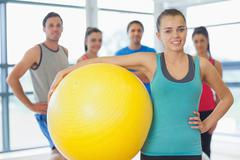 Instructor holding exercise ball with fitness class in background - stock photo