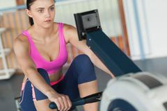 Woman working out on row machine in fitness studio Stock Photos