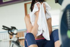 Tired young woman wiping face while working on row machine - stock photo