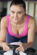 Portrait of a smiling woman working out at spinning class Stock Photos