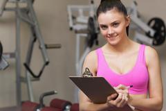Stock Photo of Smiling female trainer writing on clipboard in gym