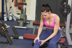 Healthy woman with an injured knee sitting in gym - stock photo