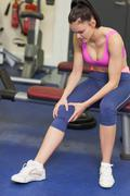 Healthy woman with an injured knee sitting in gym Stock Photos