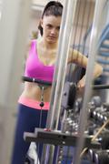 Stock Photo of Determined woman doing exercises in gym on lat machine