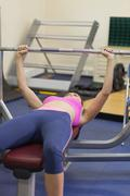 Stock Photo of Fit woman lifting the barbell bench press in gym