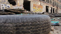 Tire in foreground silhouettes abandoned industrial building(HD) k Stock Footage