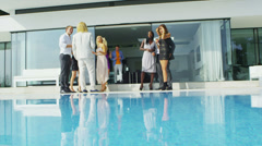 Glamorous friends enjoying drinks by the pool outside luxury modern home - stock footage