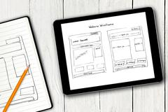 Website wireframe sketch on digital tablet screen Stock Photos