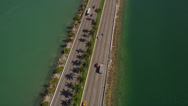 Stock Video Footage of Wide birdseye aerial shot of medium traffic on the MacArthur Causeway, tilt up