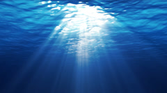 Underwater scene with sunrays shining through the water's surface - stock footage