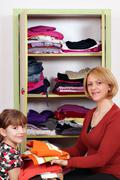Mother and daughter agrees clothes in a closet Stock Photos