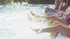 Friends enjoying summer pool party splashing and kicking legs in the water - stock footage
