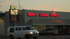 Vehicles pass by liquor store in the setting sun Stock Footage