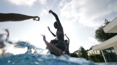 Happy fun loving group of friends playing in the water at summer pool party - stock footage