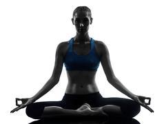 Woman exercising yoga meditating silhouette Stock Photos