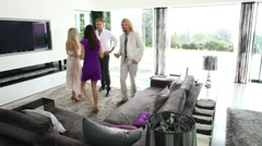 Timelapse of glamorous friends chatting over cocktails in luxury modern home Stock Footage