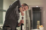Stock Video Footage of Young handsome man opening bottle with wine in kitchen NTSC
