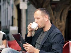 Young man with tablet computer drinking coffee in cafe NTSC Stock Footage