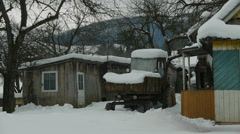 Snow-covered old tractor parked in the yard. Carpathians, Ukraine. Stock Footage