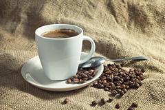Stock Photo of warm cup of coffee with coffee beans.