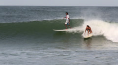 Two surfers riding a wave and wiping out Stock Footage