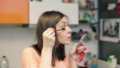 Young beautiful woman dyes her eyelashes in home HD Stock Footage