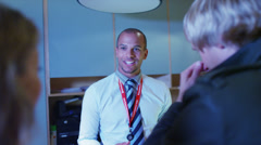 Helpful staff dealing with customers at business reception area - stock footage