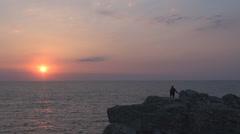 Man person silhouette admire sunset sunrise sun ocean rocky cliff resort island Stock Footage