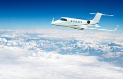Airplane fliying over the clouds Stock Photos