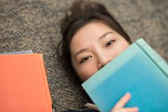 student laying on carpet with books - stock photo