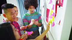 Young creative business team brainstorming with the use of post-it notes Stock Footage