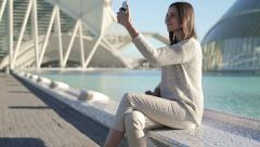 Young woman taking photo of herself with smartphone in city HD Stock Footage