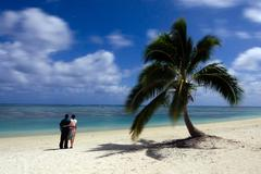 Young couple watches the stars at night on deserted tropical island Stock Photos