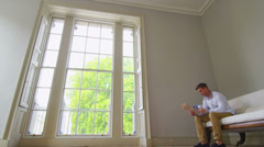 Young man in elegant apartment gets up to take look out of the window - stock footage
