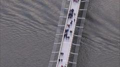 Aerial view of pedestrians crossing London's Millennium bridge Stock Footage