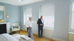 Attractive senior couple in evening wear getting dressed for an evening out Stock Footage