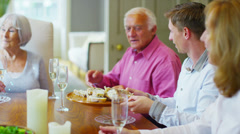 3 generations of a happy family together at home, sharing food & drinking wine - stock footage
