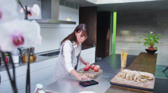 Attractive young woman preparing meal and following a recipe on computer tablet - stock footage
