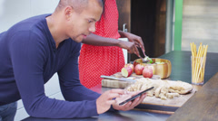 Attractive young couple preparing meal and following a recipe on computer tablet - stock footage