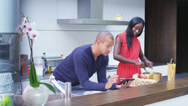 Stock Video Footage of Attractive young couple preparing meal and following a recipe on computer tablet
