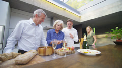 Happy adult family group chatting and preparing lunch in modern kitchen - stock footage