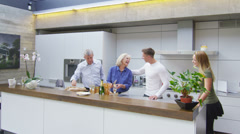 Happy adult family group greeting each other in the kitchen of the family home - stock footage
