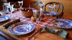 woman setting dining table for thanksgiving dinner - stock footage
