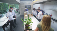 Happy group of family & friends greet each other in the kitchen of modern home.  Stock Footage