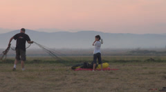 Father son prepare parachute take off land man child wire meadow pasture sunset Stock Footage