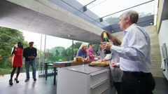 Happy group of family & friends drinking champagne in the kitchen of modern home - stock footage
