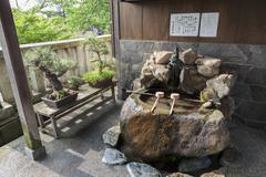 Purification ladles and bonsai trees in the kanazawa old town, japan. Stock Photos
