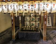 fragment of a shinto shrine with purification ladles, sake offerings and whit - stock photo